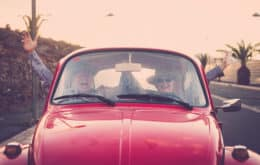 Happy senior couple on vacation going for a drive in red volkswagen beetle