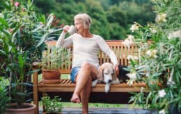 Senior woman with her dog drinking coffee while sitting outdoors surrounded by flowers