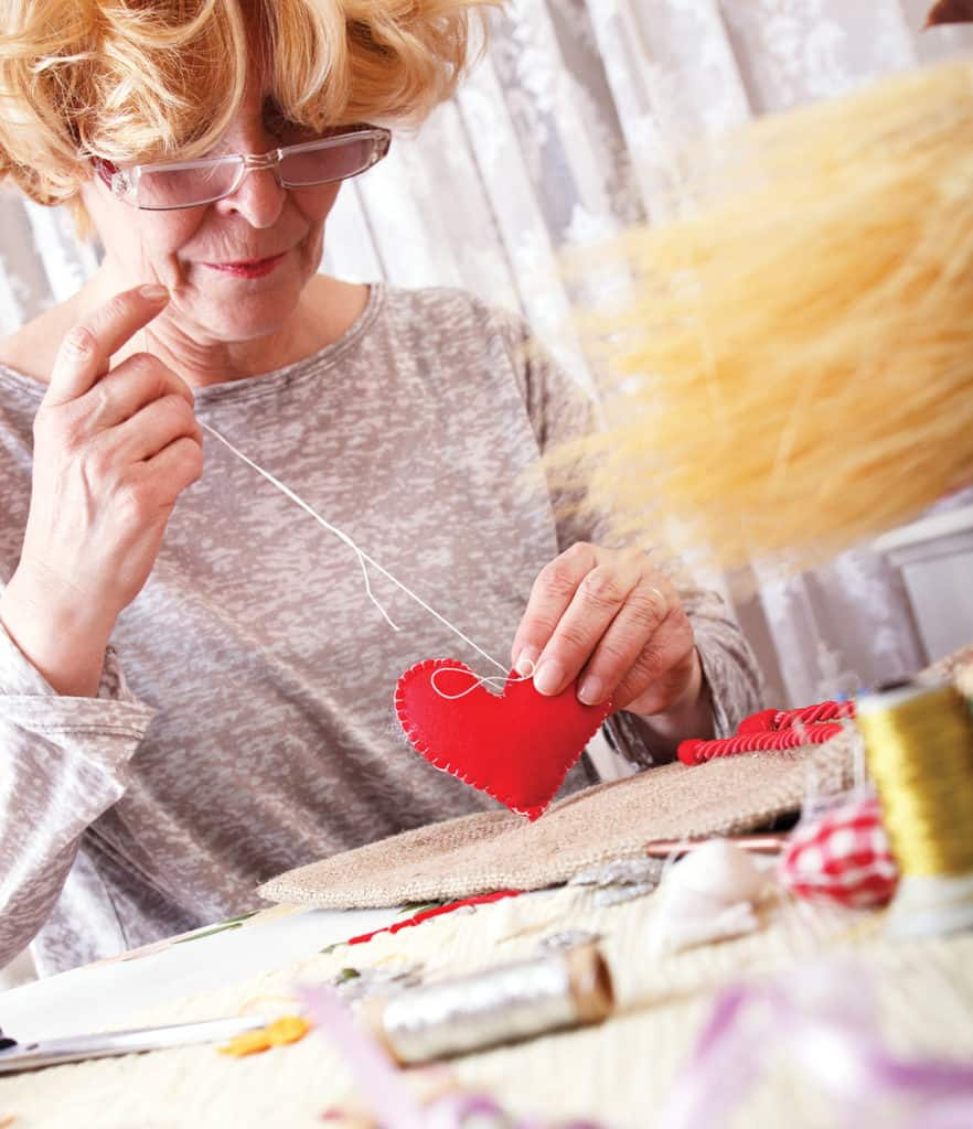 Senior woman crafting a felt heart
