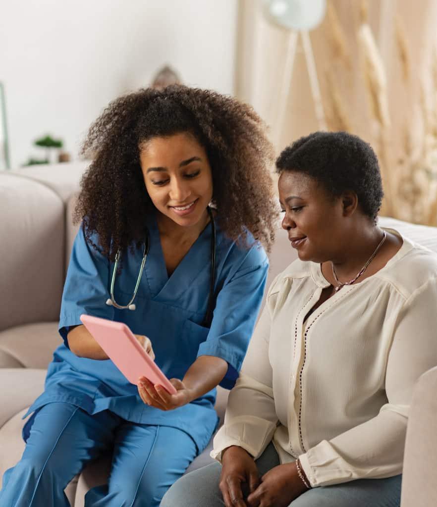 Pleasant nurse showing online news to elderly lady