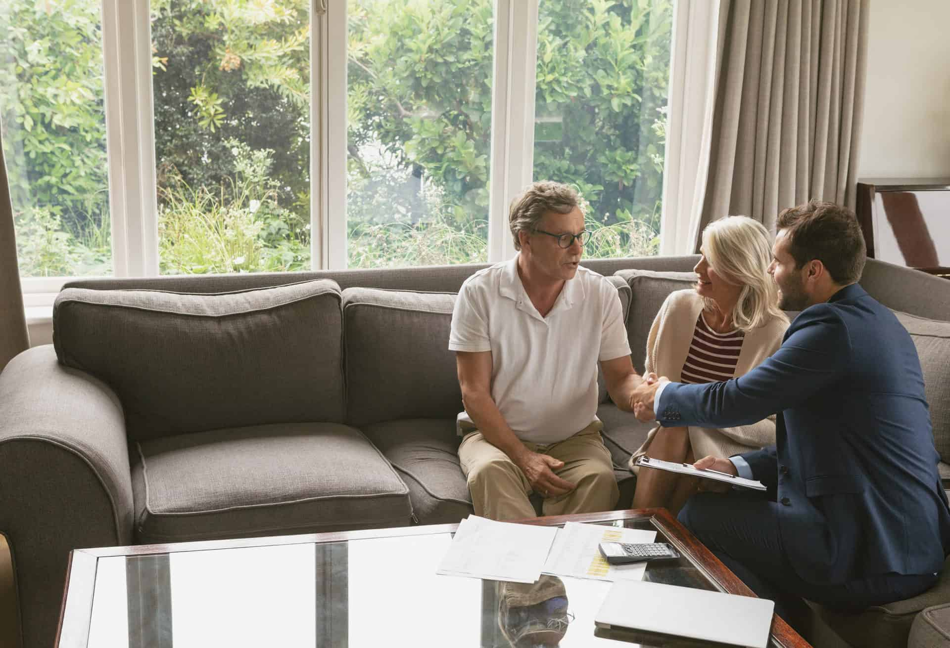 Active senior man shaking hands with financial advisor in living room
