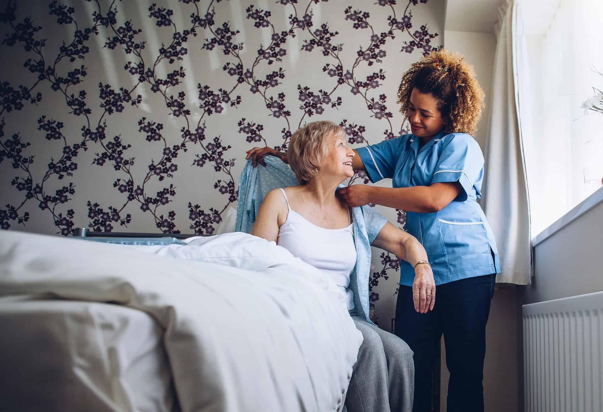Caregiver helping senior woman to get dressed