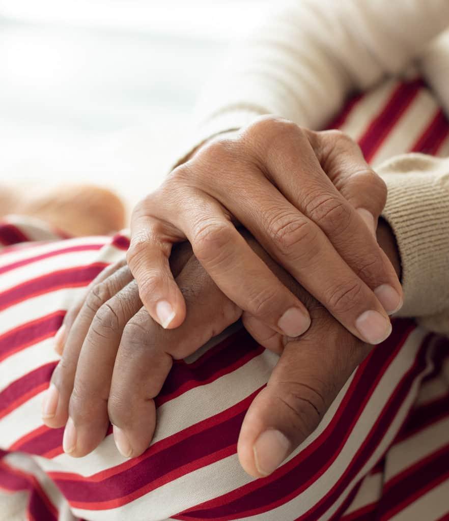 Companion with hand over seniors hand