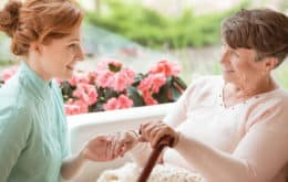 Senior woman sitting next to flower with caregiver while holding her hand
