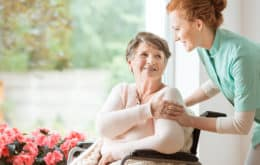 Nurse helping an elderly woman in a wheel chair sitting next to red flowers.