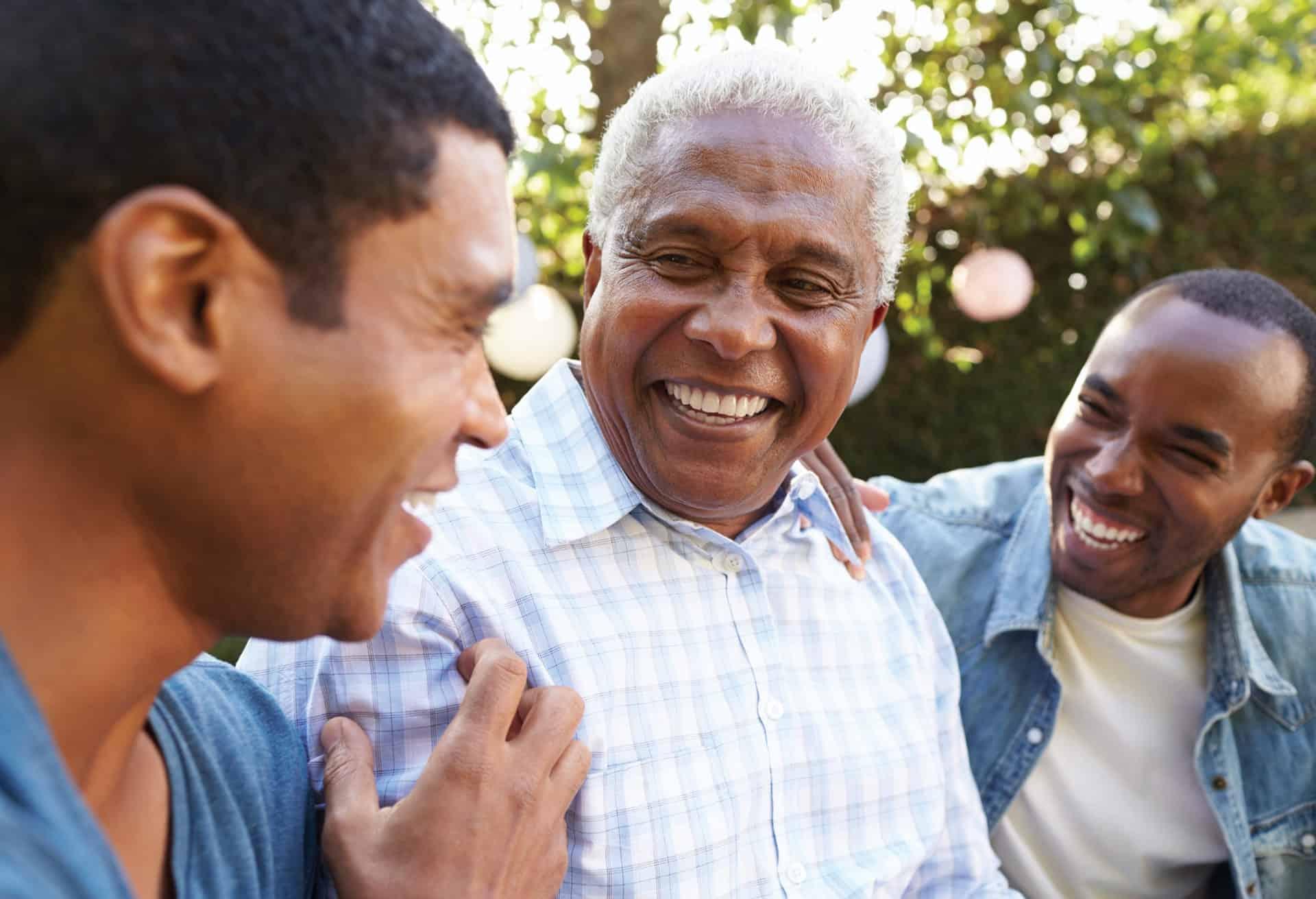 Senior man enjoying talking with his adult sons in garden