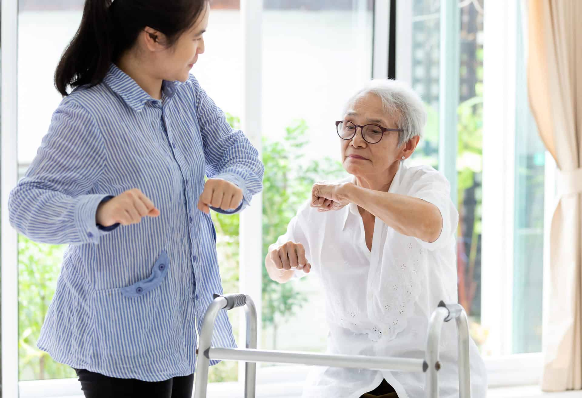 Elderly woman doing rehabilitation exercise with trainer
