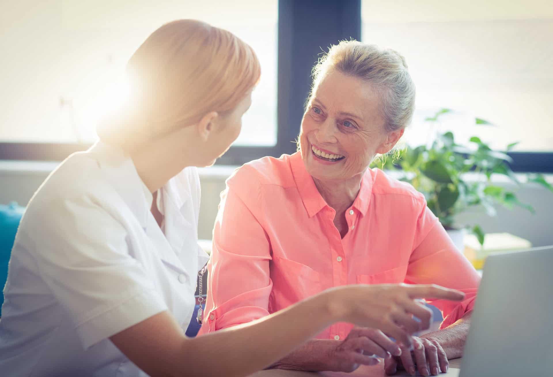 Smiling senior woman speaking with caregiver.