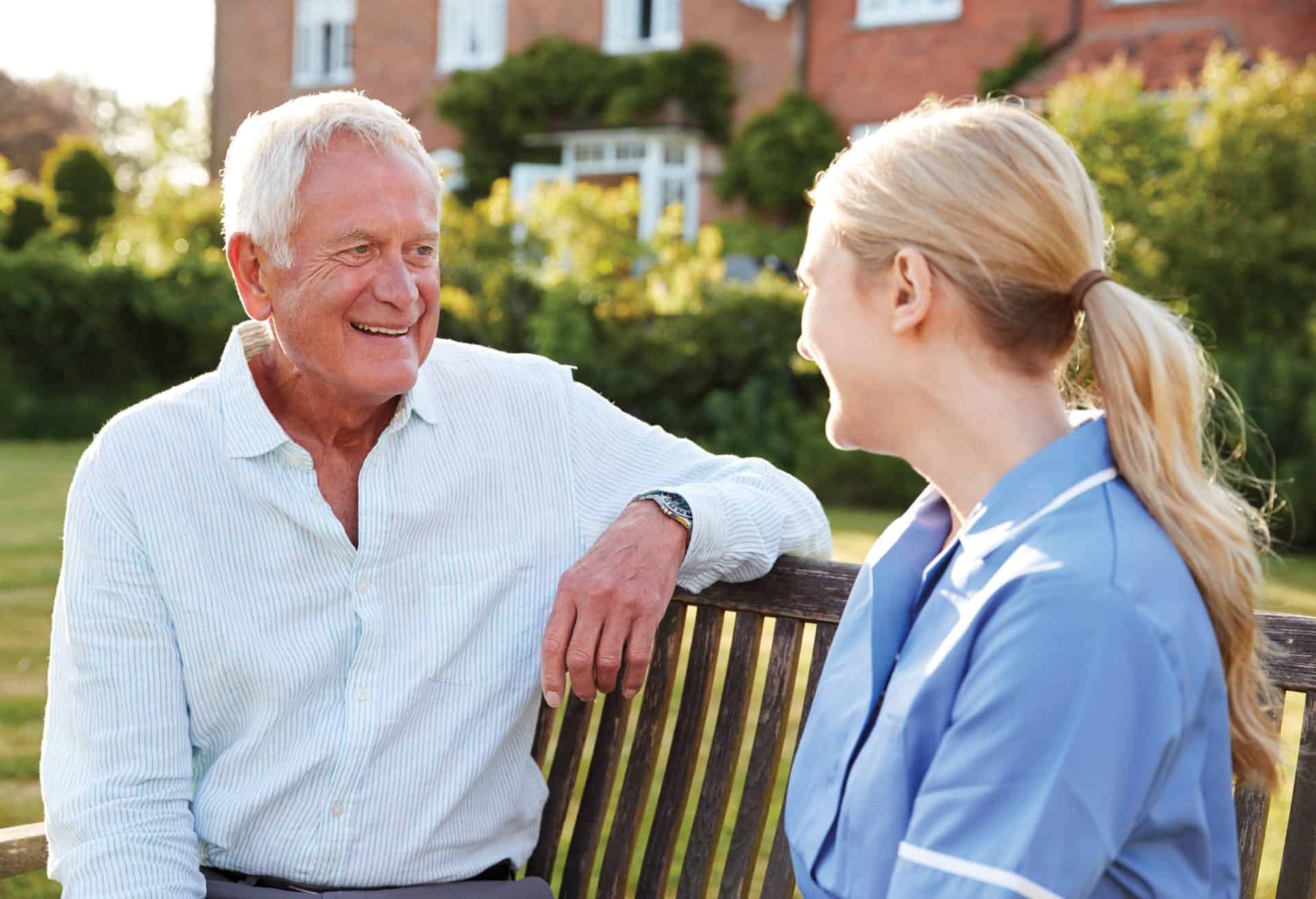 Senior man talking with a caregiver outside on bench.
