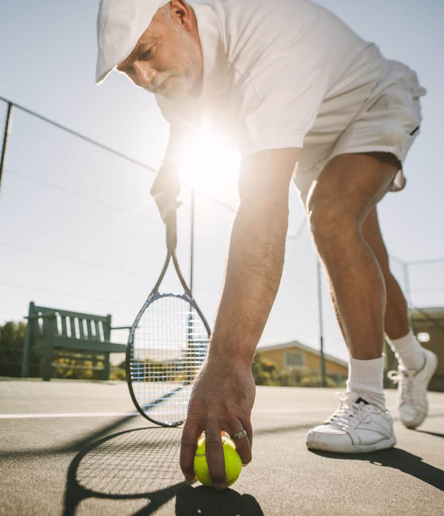 Low angle view of a tennis player bending forward to pick the ball