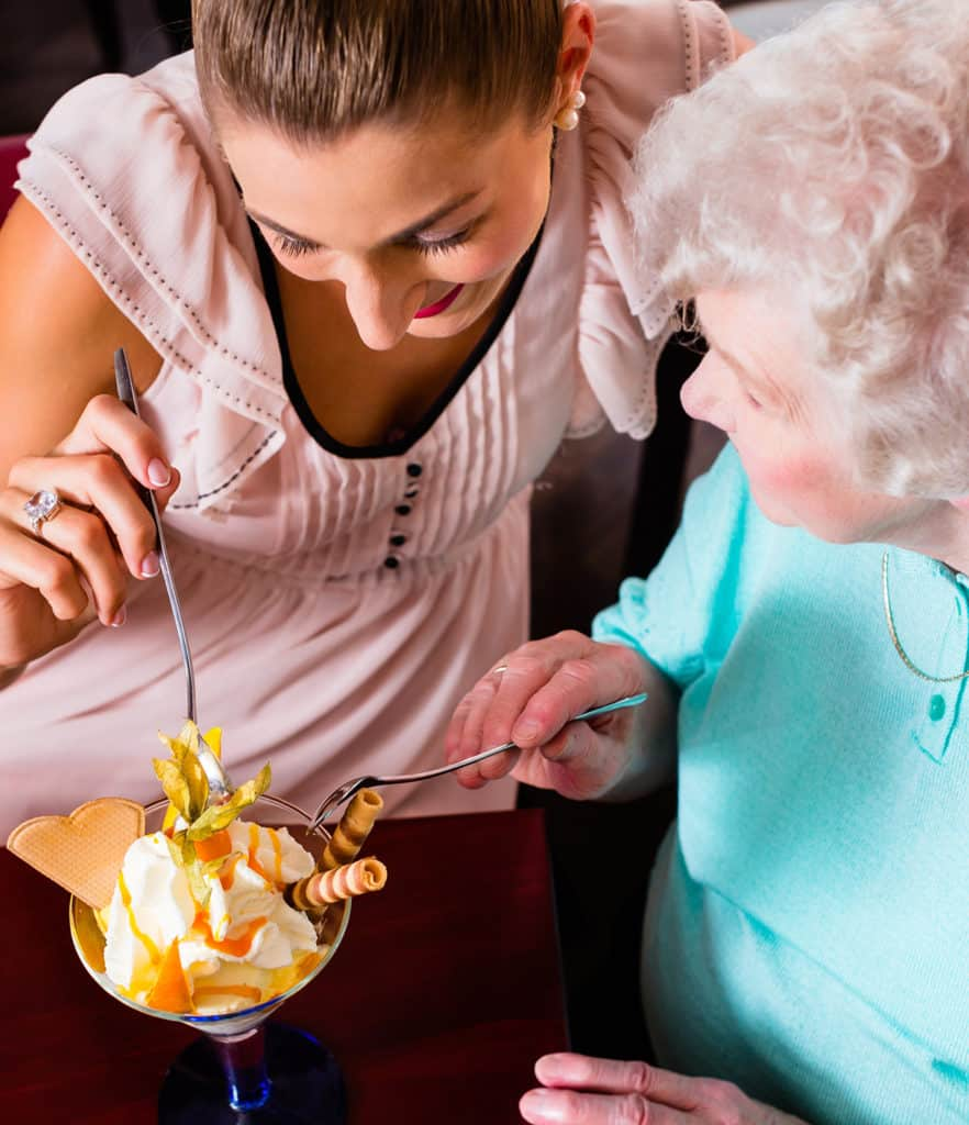 Senior woman and granddaughter having fun eating ice cream sundae in cafe.