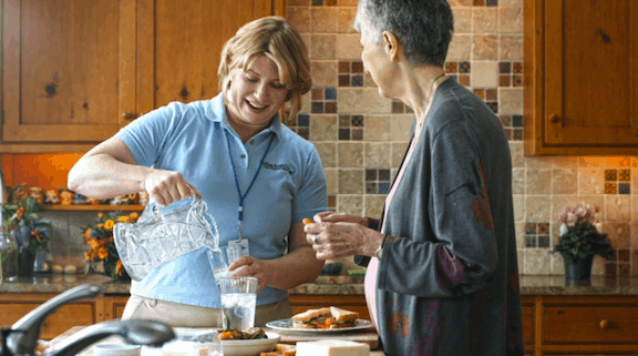 Home health aid pouring senior a glass of water