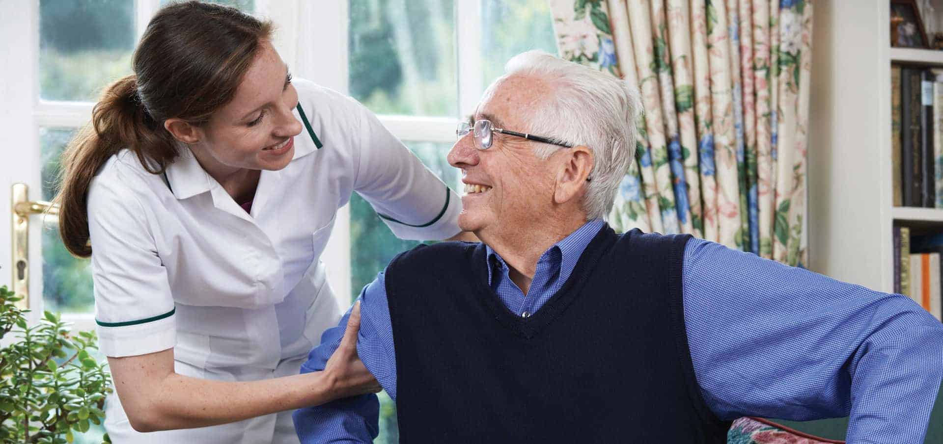 home care aide helping senior man out of chair