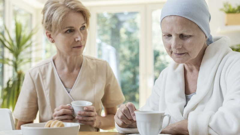 Sad senior woman and caregiver drinking tea in the nursing house