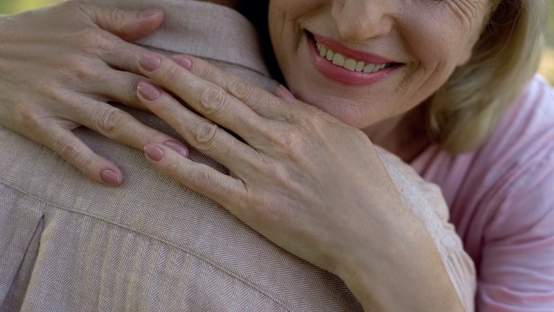 Old woman hugging man closeup, family support and love, trusting relationship