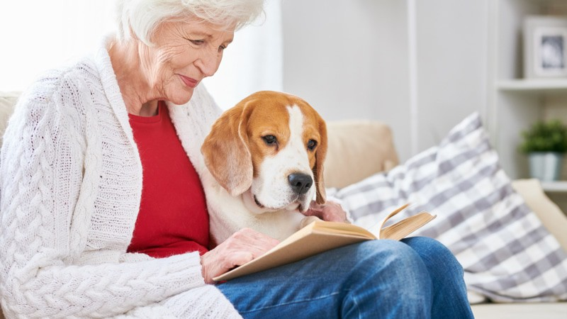 """Loving Senior Woman Reading """"Changing Minds"""" with Dog"""
