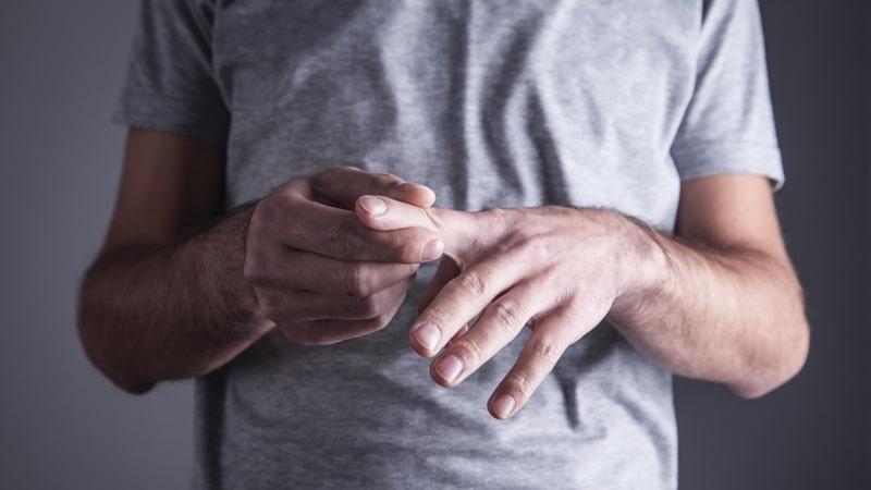 Caucasian man with finger ache. Arthritis, wrist pain