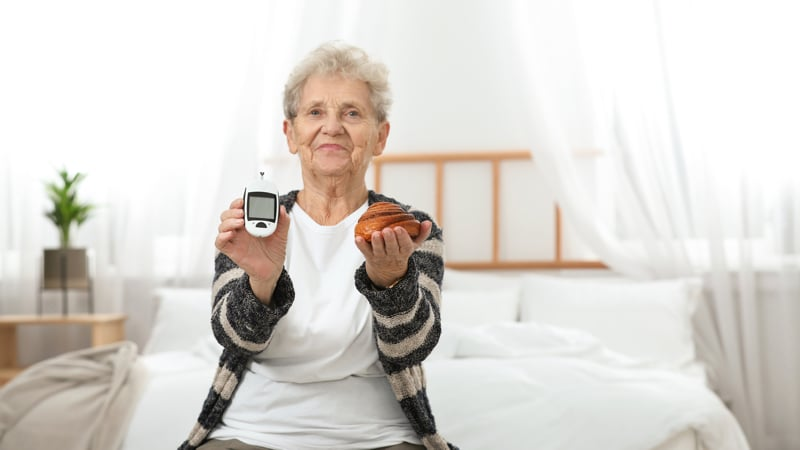 Senior woman holding digital glucometer and pastry at home. This is how to manage diabetes without medication