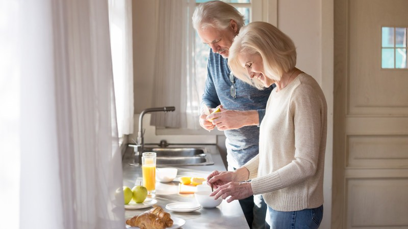 Happy senior couple make healthy breakfast in home kitchen to prevent falls
