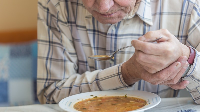 Man with signs of Parkinson's disease tries to eat Campbell's bean soup