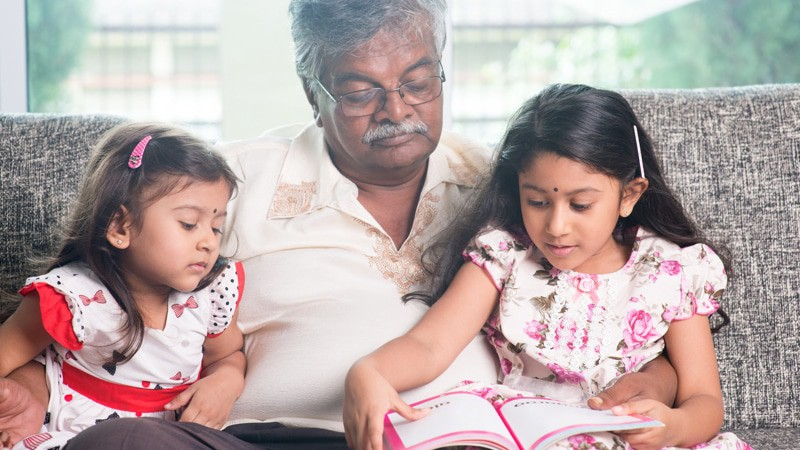 This man knows how to entertain the grandkids. Grandparent and grandchildren reading story book.