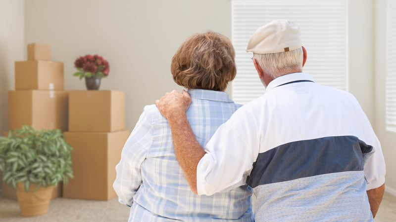 Two seniors look while they pack for assisted living
