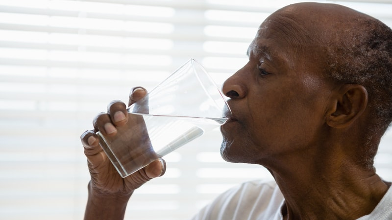 Senior man drinking water and no longer suffering from dehydration