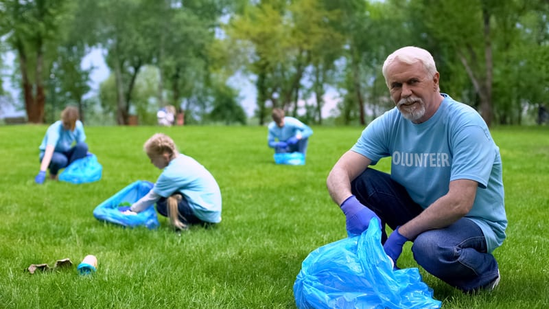 Senior volunteering by picking up trash