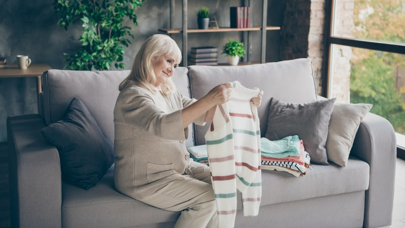 Senior woman downsizing her clothes pile on the couch