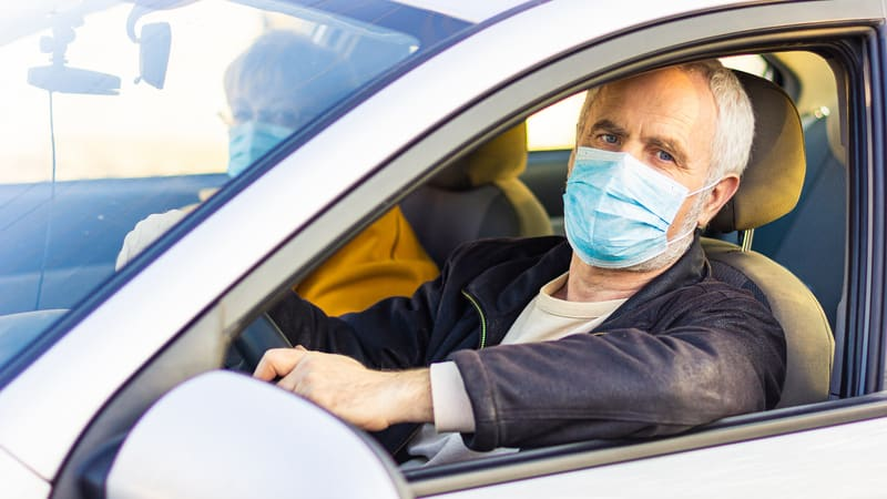 Man and his wife going on a road trip with a coronavirus mask on