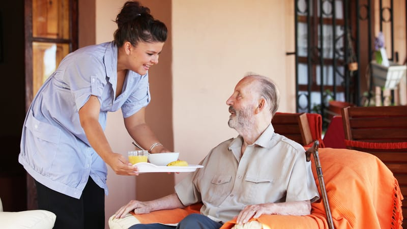 Non-medical home care aide giving some guy lunch
