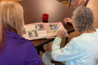 American Senior Communities Caregiver With Resident Reading