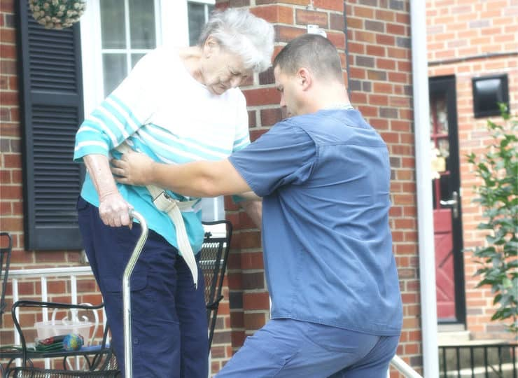 Stay Well Home Health Male Caregiver Helping Elderly Lady Down the Stairs