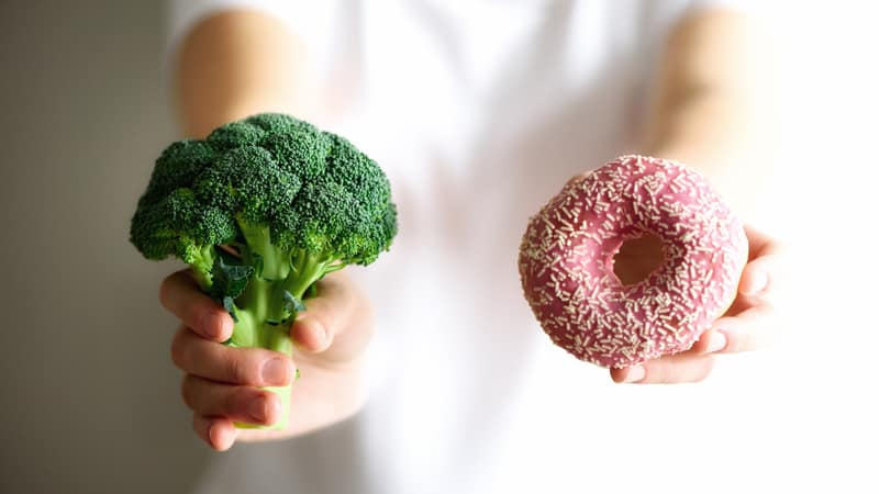 Person eating broccoli instead of donuts because of sugar detox