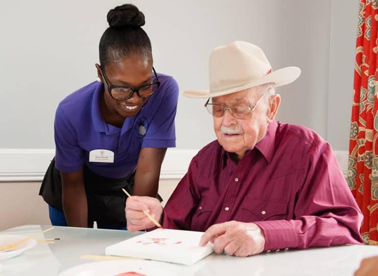 Commonwealth Senior Living Hampton Senior Man Painting with Caregiver
