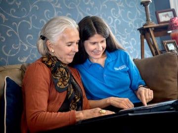 Senior Helpers Caregiver with Senior Lady Looking at Photo Album