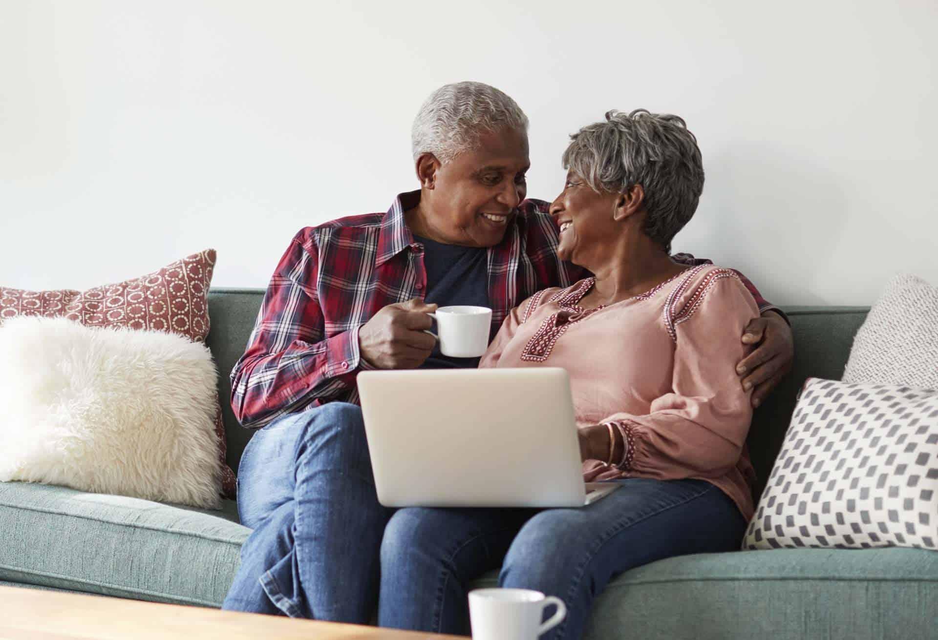 Senior couple searching living options on laptop