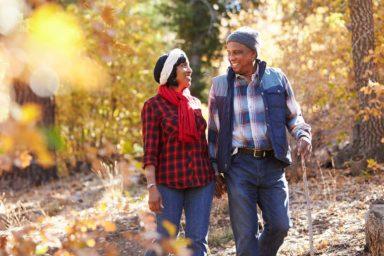 Happy Senior Couple walking in the autumn woods