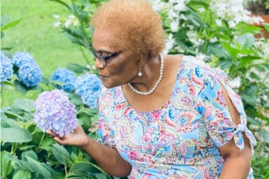 Cassiopeia's Home Care Elderly Lady Smelling Flower Outside