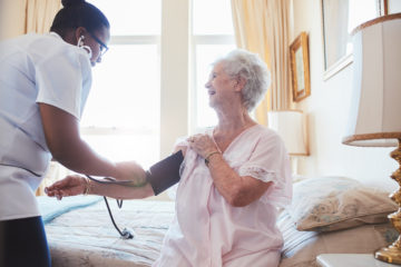 Home Care aide checking seniors blood pressure