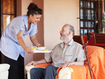 Grace Care Solutions Caregiver Handing Food to Elderly Man
