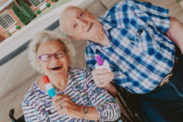 Smiling Senior Couple outside with popsicles
