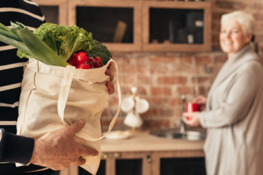 Woman and man in the kitchen, with vegetables in a canvas bag. For article, Be Green in the Kitchen