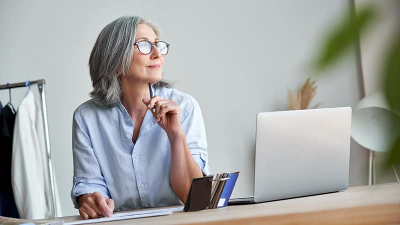 Inspired woman pondering her work. For article on starting a new career after 50