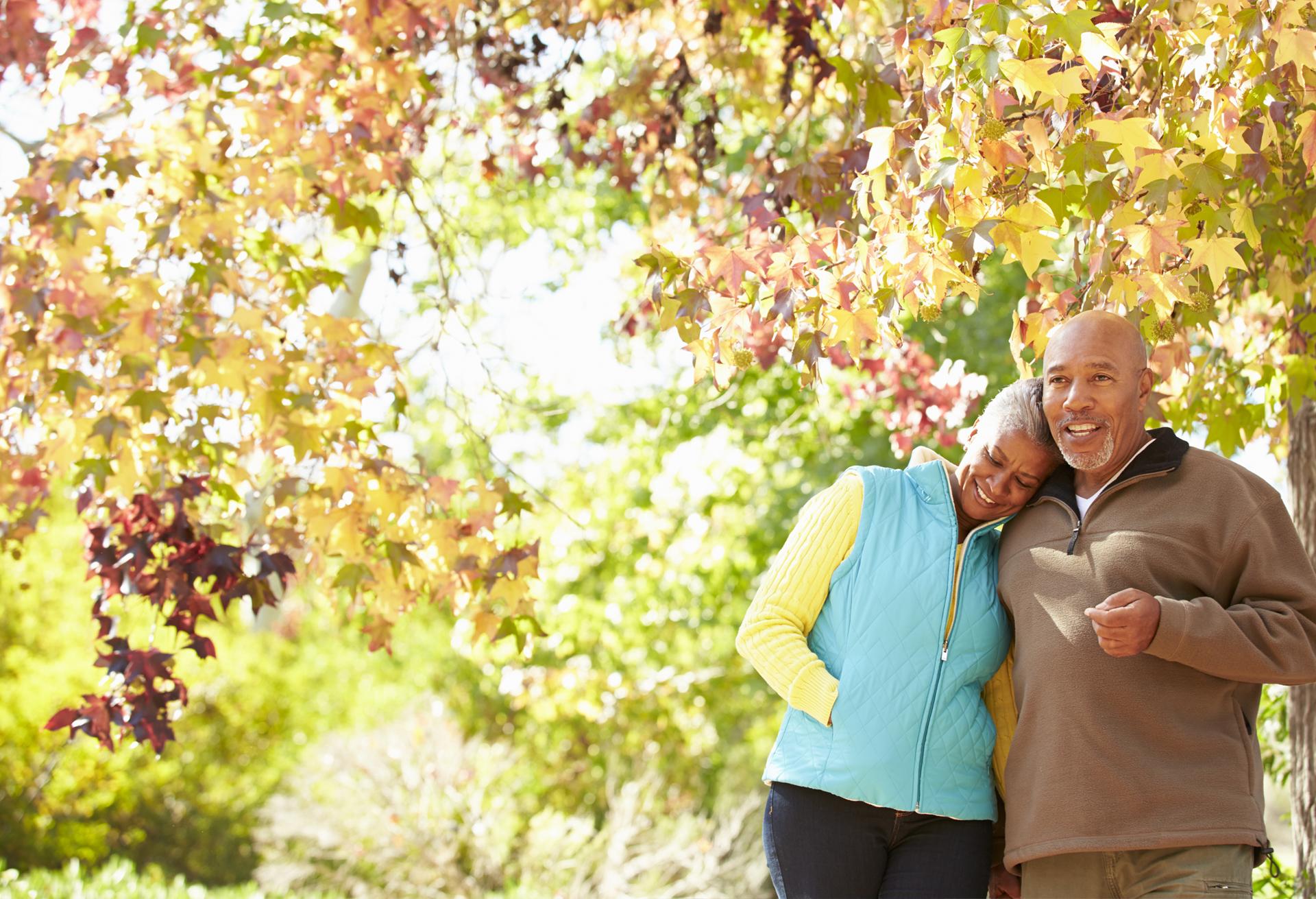 Seniors couple walking outside fall leaves