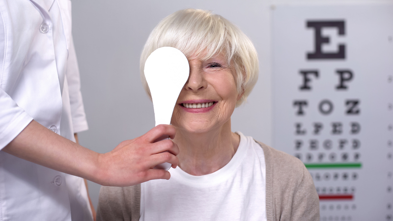 Happy older woman at an eyesight test. For article on LASIK eye surgery for seniors