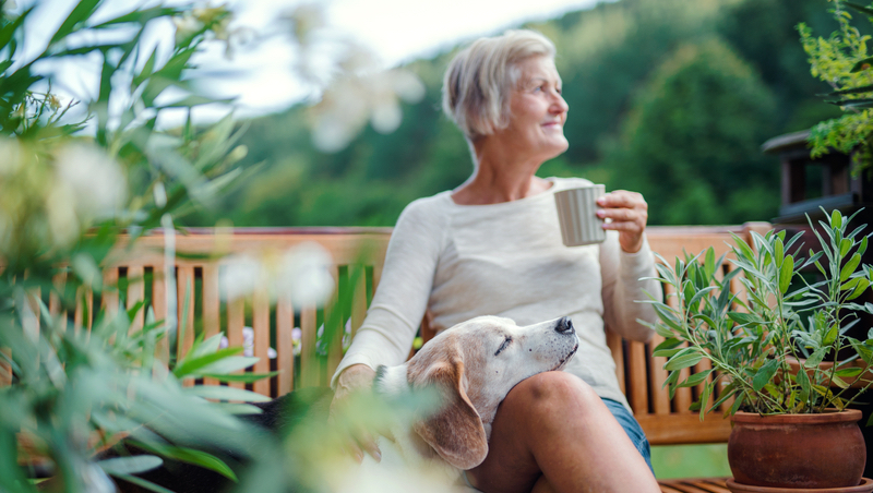 senior woman coffee dog outside (credit: Pojoslaw Dreamstime) for article on the health benefits of coffee